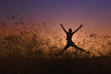silhouette of girl jumping in a meadow