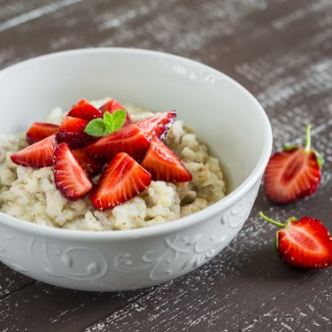 Oatmeal with honey and strawberries in a white bowl