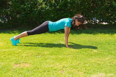 Young athletic woman does push-ups training outdoor