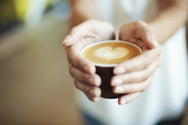 Closeup of Female giving coffee with heart symbol