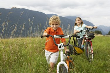 Boy and girl (5-8 years) with mountain bikes in long grass, smiling, portrait