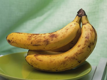 Bunch of bananas on green plate, side view