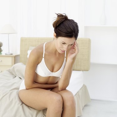 Close-up of a young woman sitting on the edge of a bed holding her stomach