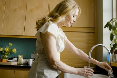 Woman pouring glass of water from faucet