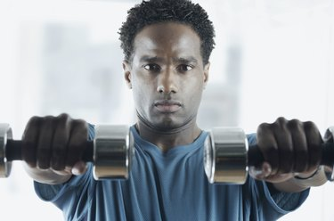Close-up of a mid adult man holding dumbbells