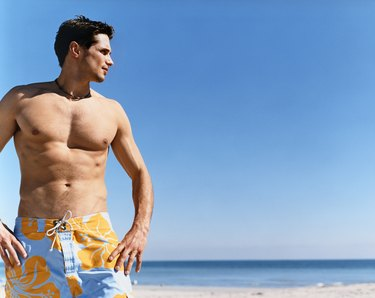 Man Standing on a Beach With His Hands on His Hips and Looking Sideways
