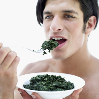 Portrait of a young man eating spinach with fork