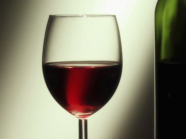 Glass of red wine besides wine bottle