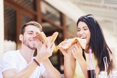 Hispanic couple eating pizza at cafe