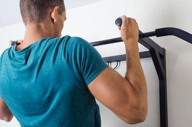 Muscular man doing pull ups at gym.