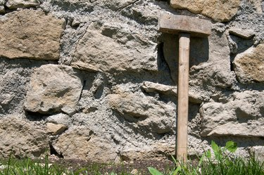 Sledge hammer leaning against stone masonry wall