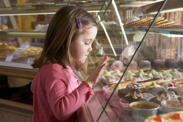 Young girl (9-11) looking at cakes in display cabinets, side view