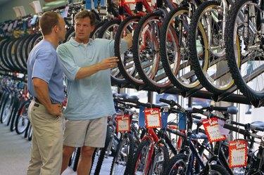 Salesman helping man shop for bike