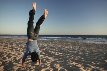 Man doing handstand on beach