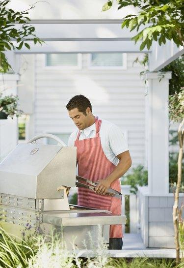 Hispanic man next to barbecue