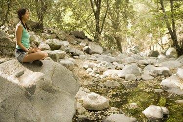 Woman seated on rock meditating