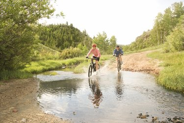 Women riding bicycles through mud pond