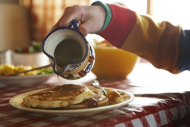 Teenage boy (13-14) pouring syrup on pancakes
