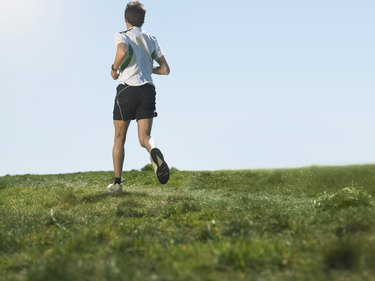 Mid adult man jogging on grass, rear view