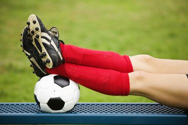 Soccer player resting feet on ball
