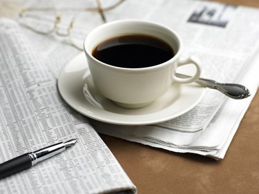 Cup of coffee, pen and financial newspaper