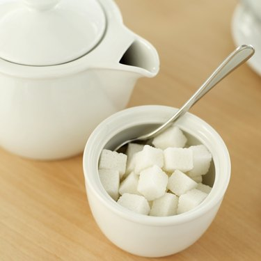 high angle view of a teapot and a bowl of sugar cubes with a spoon