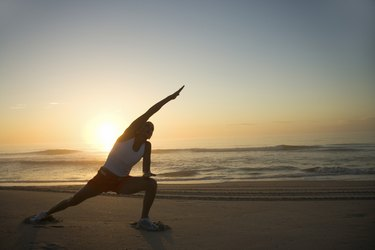 Woman stretching at beach at sunrise