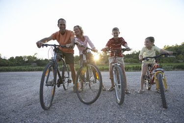 Family with daughter (7-9) and son (11-13) riding bicycles, low angle view