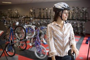 Woman in safety helmet in bike shop