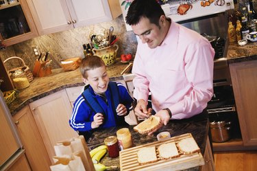 Father making peanut butter and jelly sandwich for son
