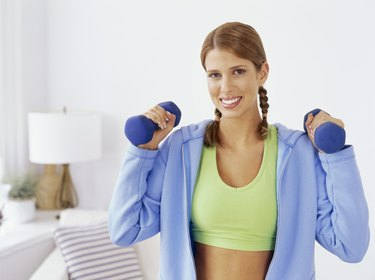 portrait of a young woman working out with dumbbells