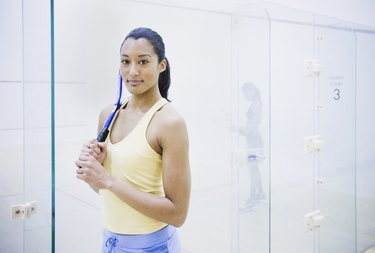 Woman holding Squash racket indoors