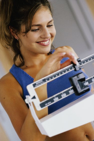 Close-up of a young woman adjusting a weight scale