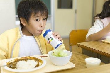 Boy drinking milk at desk