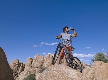 African man with mountain bike on rocks