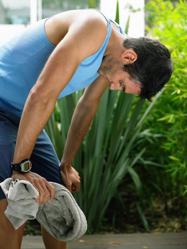 Man in sports clothes bending over, catching breath in garden