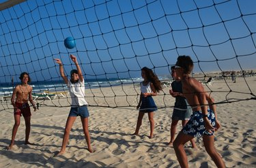 Teenage girls and boys (16-17) playing beach volley ball