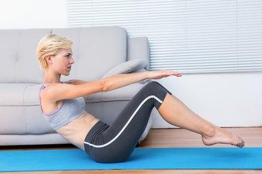 Fit blonde woman doing sit ups