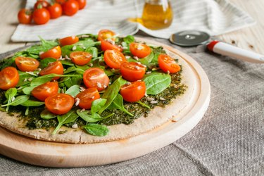Pizza with pesto, spinach and cherry tomatoes