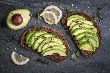 Avocado sandwich on dark rye bread made with fresh sliced avocados.