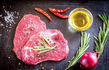 Fresh beef steaks with ingredients on the dark background