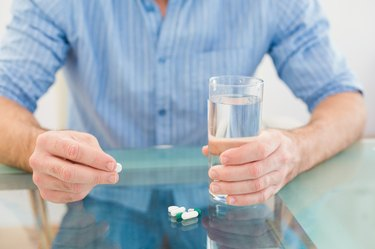 Casual businessman holding glass of water and tablet