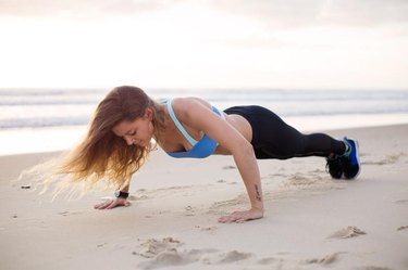 A woman exercises on the beach by doing push ups.