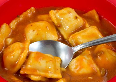 Ravioli in a red bowl with a spoon