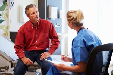 Patient And Female Doctor Have Consultation In Hospital Room