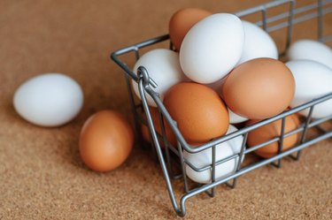 White and brown eggs in metal basket close up