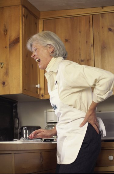 Woman standing in a kitchen holding her back in pain