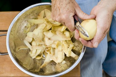 Person's hands peeling potatoes