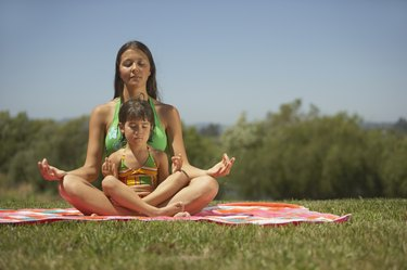 Mother and daughter meditating together