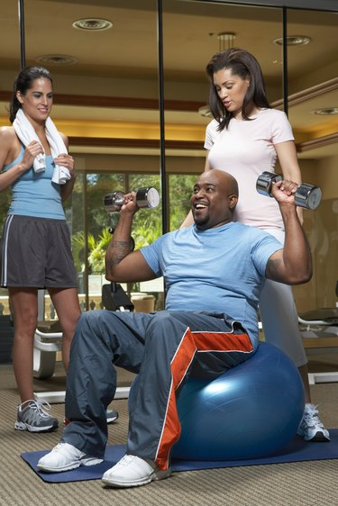 Woman giving weight training to man with dumbbells, smiling